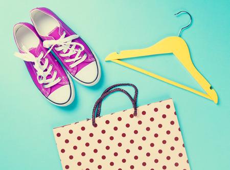 morado: sabuesos de color p�rpura con cordones blancos y percha con bolsa de compras en fondo azul.