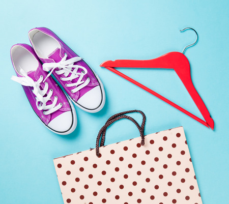 purple gumshoes with white shoelaces and hanger with shopping bag on blue background. photo