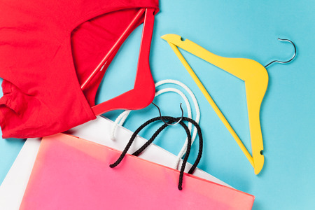 clothes shopping: Shopping bags and hangers with red dress on blue background Stock Photo