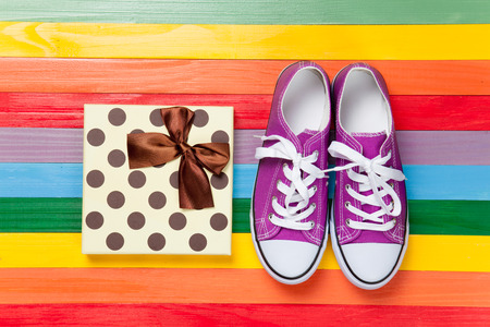 Gumshoes with white shoelaces on multicolor wooden background. photo
