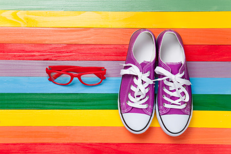 Gumshoes with white shoelaces and glasses on multicolor wooden background. photo