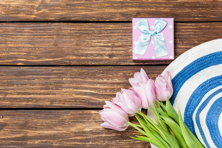hat, gift box and tulips on a wooden background photo