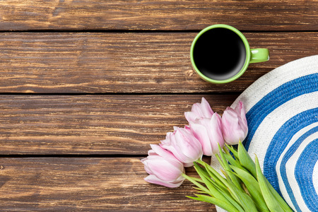 spring hat: Hat and cup of coffee with tulips on a wooden background