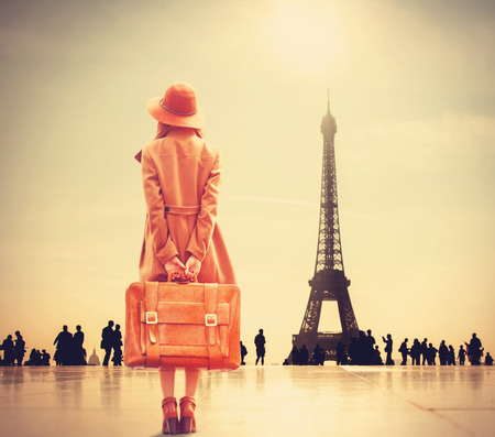 vintage woman: Redhead girl with suitcase on Eiffel tower background