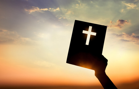 Hand holding book with cross on sunset background