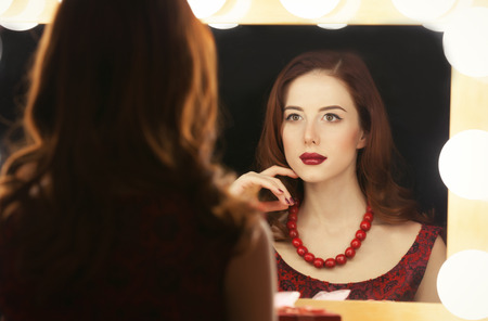 mirror: Portrait of a beautiful woman as applying makeup near a mirror. Stock Photo