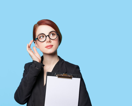 Portrait of thinking business women in glasses on blue background photo