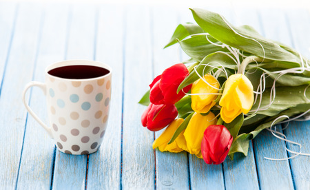 Cup of coffee and bouquet of tulips on blue table. photo