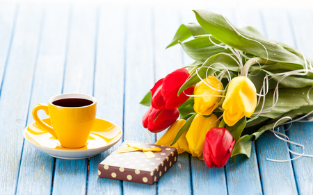Cup of coffee and gift box with bouquet of tulips on blue table. photo