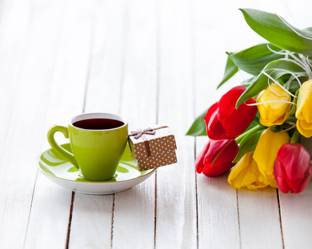 Cup of coffee and gift box with bouquet of tulips on white table. photo