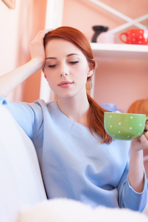 Redhead girl in blue blouse with green cup sitting on sofa at home photo