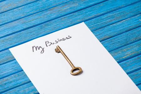 protecting your business: Clave y papel con mis palabras de negocios sobre fondo azul