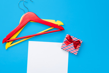 paper hanger: hangers and gift near paper on blue background