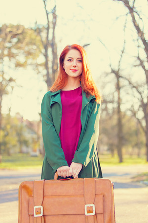 beautiful redhead: Beautiful redhead girl with suicase in the park Stock Photo