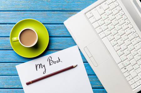 Coffee and paper with My Book inscription near notebook on blue wooden table