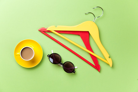hangers: Cup of coffee and hangers with sunglasses on green background. Stock Photo