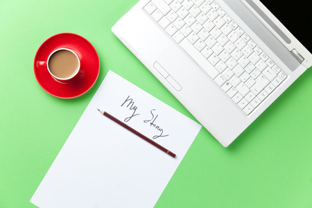 Cup of coffee and paper with inscription and computer on green background.