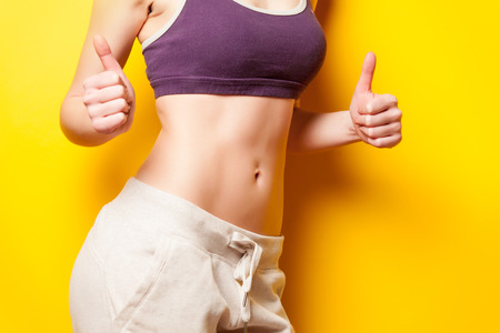 show off: Woman showing her abs after weight loss on yellow background Stock Photo
