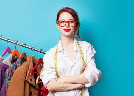 working model: Young redhead designer with metric and clothes on blue background
