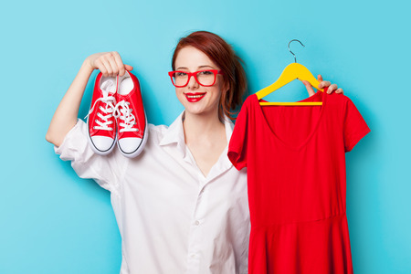 the designer: Young redhead designer with dress and gumshoes on blue background