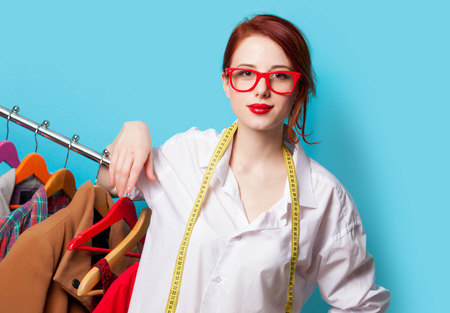metric: Young redhead designer with metric and clothes on blue background