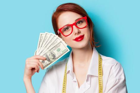 青色の背景にお金と赤の眼鏡赤毛の女性の肖像画 写真素材