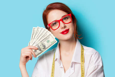 woman pose: Portrait of redhead women in red glasses with money on blue background