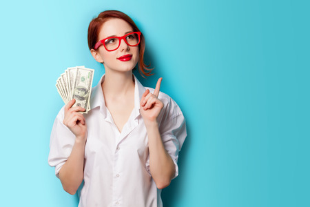 earnings: Portrait of redhead women in red glasses with money on blue background