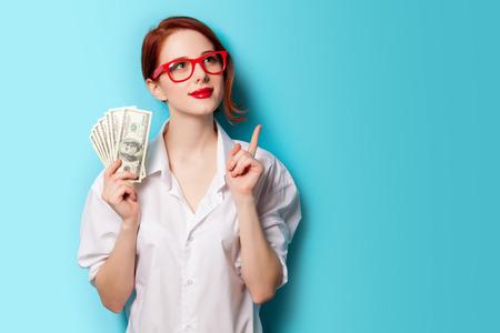 pelirrojas: Retrato de la mujer pelirroja en vidrios rojos con dinero sobre fondo azul Foto de archivo