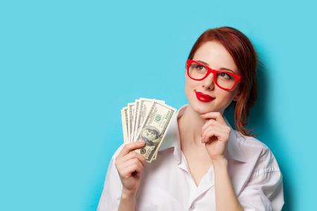 青い背景の金で赤いメガネの赤毛の女性の肖像画
