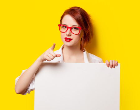 Surprised student girl in white shirt and glasses with white board on yellow background