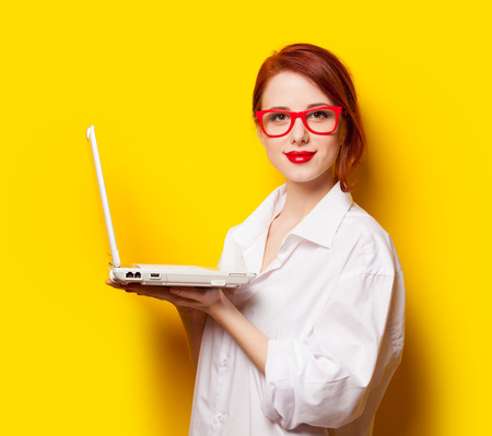 yelllow: Happy redhead girl in white shirt with computer on yelllow background.