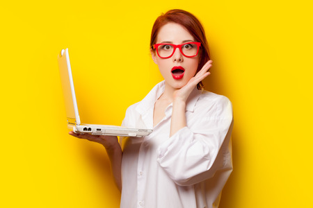 Surprised redhead girl in white shirt with computer on yelllow background. Stock Photo