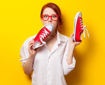yelllow: Surprised redhead girl in white shirt with gumshoes on yelllow background. Stock Photo