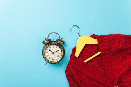 Alalrm clock and hanger with sweater on blue background. photo