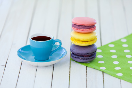 Cup of coffee and macarons on polka dot napkin and wooden table. photo
