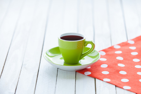 cosiness: Cup of coffee or tea on polka dot napkin and white wooden table.