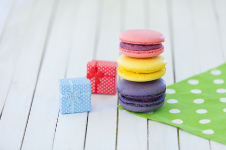 Three macarons near gifts on polka dot napkin and wooden table photo