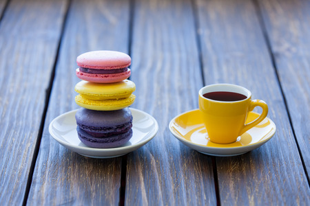 Cup of coffee and macarons on old wooden table. photo