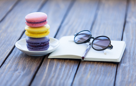 Macarons and little notebook with glasses on wooden table. photo