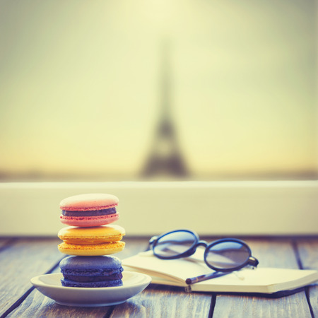 paris: Macarons and little notebook with glasses on wooden table and Eiffel tower background Stock Photo