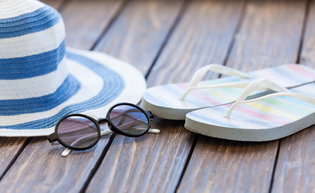 flip flops: Sunglasses and hat with flip flops on wooden table. Stock Photo
