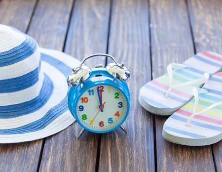 flip flops: Alarm clock and hat with flip flops on wooden table.