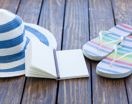 flip flops: Notebook and hat with flip flops on wooden table.