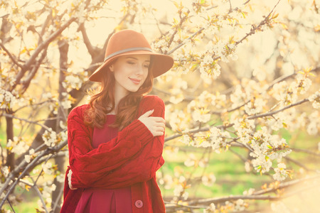 spring hat: Portrait of a beautiful redhead women in red sweater and hat in blossom apple tree garden in spring time on sunset.