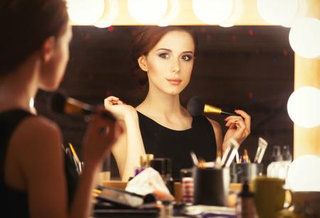 鏡に近いメイクを適用すると美しい女性の肖像画。レトロな色のスタイルの写真。