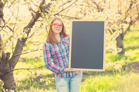 Young teen girl with blackboard in the blossom apple garden photo