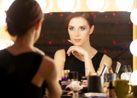 Portret van een mooie vrouw als make-up in de buurt van een spiegel. Foto in retro kleur stijl.
