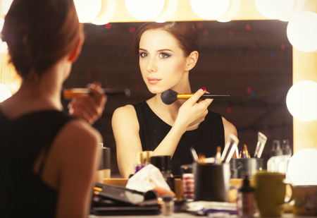 Portrait of a beautiful woman as applying makeup near a mirror. Photo in retro color style.
