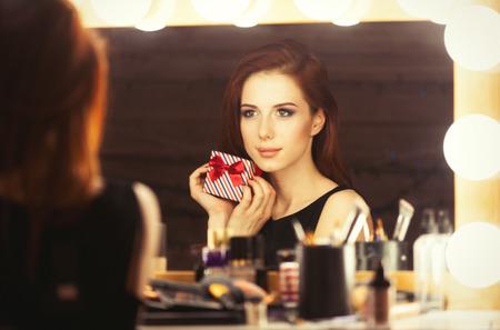 mujer maquillandose: Retrato de una bella mujer con caja de regalo cerca de un espejo maquillador. Fotos en estilo retro en color.